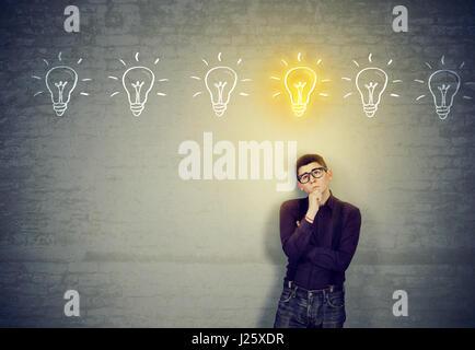 Junger Mann stützte sich auf eine Wand, auf der Suche nach der besten Lösungsidee - Stockfoto