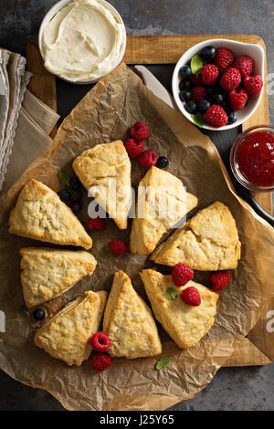 Frisch gebackene hausgemachte Scones mit Frischkäse und Früchten - Stockfoto