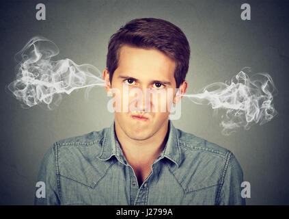 Closeup Portrait zorniger junger Mann, bläst Dampf aus den Ohren, etwa Nervenzusammenbruch isoliert grau hinterlegt - Stockfoto