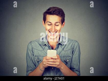 Lächelnd jungen Mann mit Blick auf seinem Smartphone SMS oder beobachten, Video, Film, Bilder auf graue Wand Hintergrund - Stockfoto