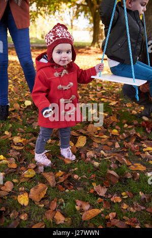 Mutter mit Kindern spielen auf Baum-Schaukel im Herbst Garten - Stockfoto