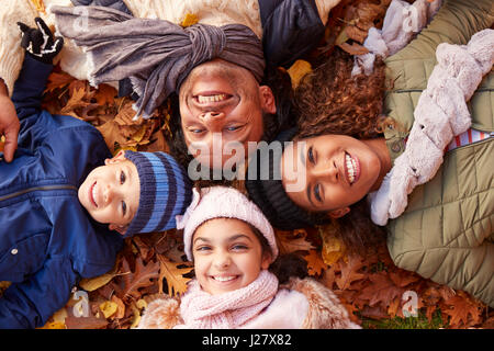 Obenliegende Porträt der Familie liegen im Herbst Blätter - Stockfoto
