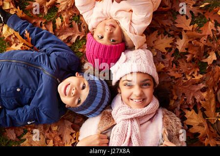 Obenliegende Porträt von drei Kindern im Herbstlaub liegend - Stockfoto