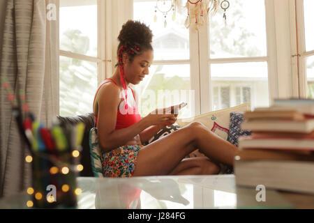 Schwarze Mädchen auf der Couch liegend und mit Smartphone, junge afroamerikanische Frau entspannend mit Handy. Glücklich Latina auf Sofa sitzen, Lächeln und tex Stockfoto