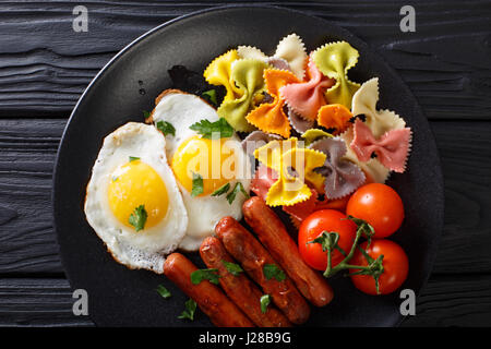 Spiegelei, Würstchen, Nudeln Farfalle und Tomate Nahaufnahme auf einer Platte. Horizontale Ansicht von oben Stockfoto
