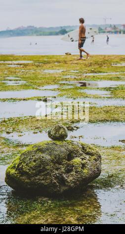 Zen-artige Steinen bedeckt mit Moos am Strand bei Ebbe, schön, Wasserreflexion, Nusa Dua, Bali, Indonesien - Stockfoto