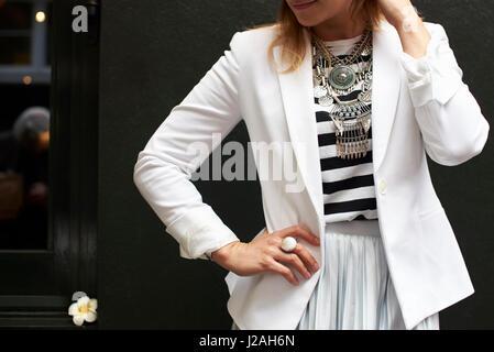 Frau in weißen Jacke und Halskette, hand auf Hüfte, Mittelteil - Stockfoto