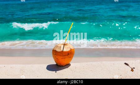Kokosnuss mit Strohhalm zu trinken, am tropischen Strand - Stockfoto