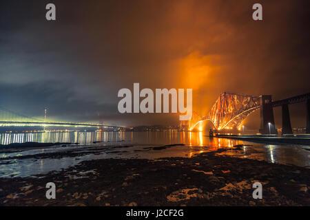 Die Forth Rail Bridge und Forth Road Bridge Grenzübergänge über den Firth River in der Nacht. South Queensferry, - Stockfoto
