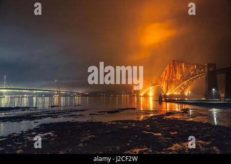 Die Forth Rail Bridge beleuchtet nachts. Goldenes Licht trifft die Wolken. South Queensferry, Edinburgh, Schottland - Stockfoto
