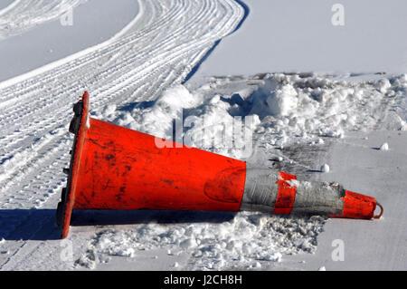Verkehr Kegel legt auf seiner Seite auf einer verschneiten und vereisten Straße in Colorado.  Schnee und Automobil - Stockfoto