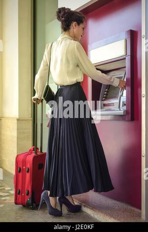 Elegante Frau unterwegs am Fahrkartenautomat