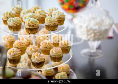 Vanilleschote Mini Cupcakes dekoriert mit Cyan und pink Candy Perlen auf klar gestaffelten Tablett auf einem Desserttisch - Stockfoto