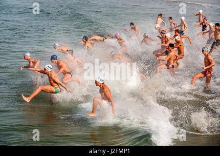 Gemischtrassig junge Erwachsene Teilnehmer für Rettungsschwimmer Sommerjobs in Newport Beach, CA, Spritzen in den - Stockfoto