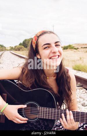 Brünette Teen Frau mit ihrer Gitarre - Stockfoto
