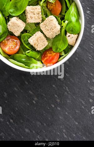 Vegane Tofu-Salat mit Tomaten und Feldsalat auf schwarzem Stein - Stockfoto
