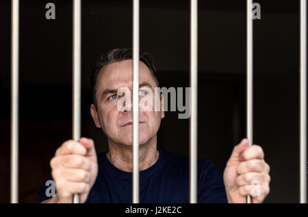 Applying blue eyed Mann inhaftiert und tragen blaues Hemd steht mit Gittern - Stockfoto