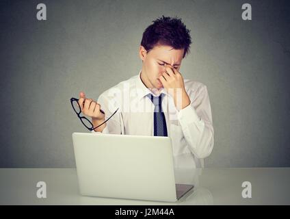 Junge müde Geschäftsmann reiben sein Auge sitzt am Tisch vor Laptop in seinem Büro - Stockfoto