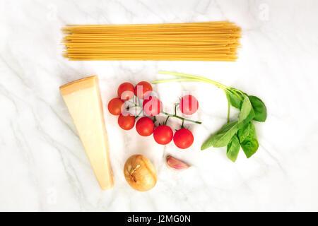 Ein Overhead Foto von grundlegenden Pasta Zutaten auf einem weißen Marmor Tisch. Frische Tomaten, eine Scheibe Käse, - Stockfoto