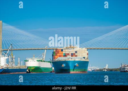 Riesige Containerschiffe unterqueren die Talmadge Memorial Bridge über den Savannah River in Savannah, Georgia, - Stockfoto