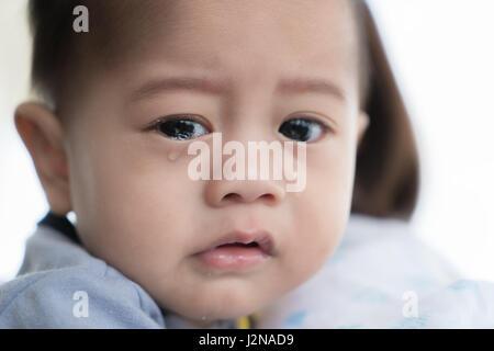Asiatischen 5 Monate jungen Weinen im Arm der Mutter. - Stockfoto