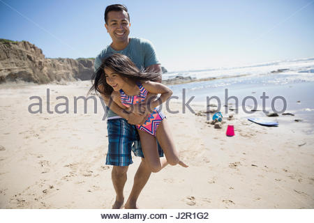 Latino-Vater mit Tochter am sonnigen Strand spielen - Stockfoto