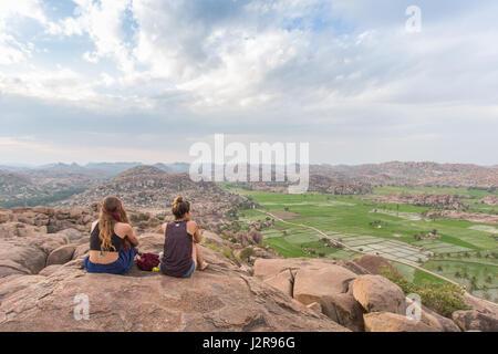 Zwei Mädchen sitzen auf einem Berg in Hampi, Indien bei Sonnenuntergang. - Stockfoto