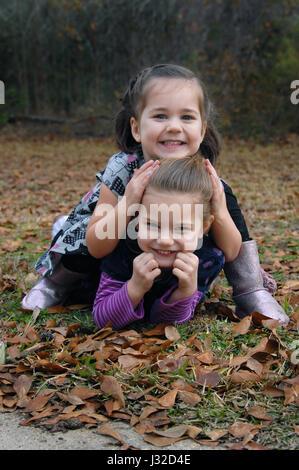 Zwei Schwestern Wäschetrockner Gras und Blätter an einem Herbst-Morgen.  Eine Schwester sitzt auf der anderen Seite - Stockfoto