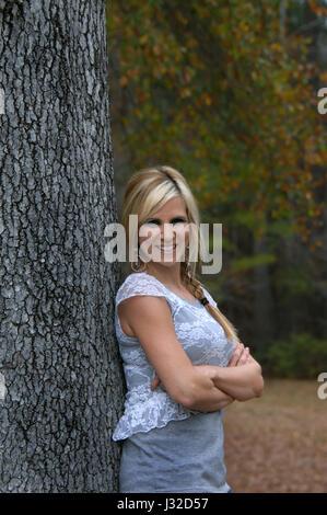 Schöne junge Frau lächelt als She lehnt sich gegen einen Baumstamm im südlichen Arkansas.  Herbst hat Blätter golden - Stockfoto