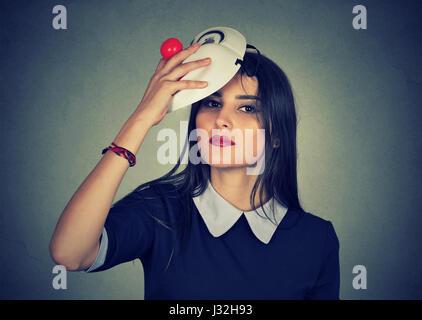 Junge Frau, die eine Maske auszuziehen. Vorgibt, jemand anderes Konzept - Stockfoto