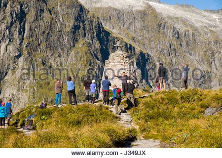 Menschen, die das Fotografieren von Kea Papagei auf das Kreuz auf den Mackinnon Memorial, Milford Track, Fjordland - Stockfoto