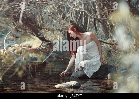 Frau, Wasser in einem Bach zu berühren. Sonnigen Wald - Stockfoto
