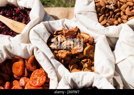 Getrocknete Aprikosen, Äpfel, Rosinen und Mandeln Nüssen in kleine weiße Leinen Säcke auf dem Display zum Verkauf - Stockfoto