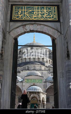 Muslimische Frau betreten den Innenhof des Sultan Ahmet oder blaue Moschee, Sultanahmet, Istanbul, Türkei - Stockfoto