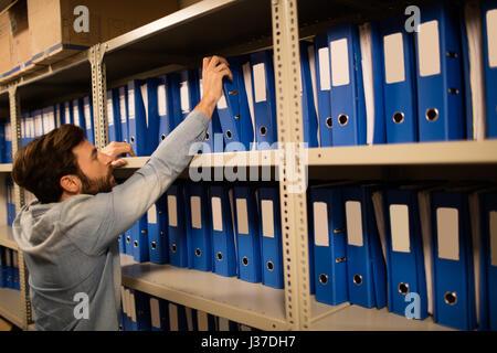 Geschäftsmann Einnahme Datei vom Regal im Abstellraum am Arbeitsplatz - Stockfoto
