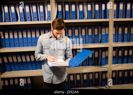 Erhöhte Ansicht der Geschäftsmann Lesung Datei stehen im Lagerraum - Stockfoto