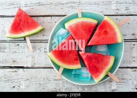 Wassermelone Stück Eis am Stiel auf einem Vintage blaue Platte und rustikale Holz Hintergrund - Stockfoto