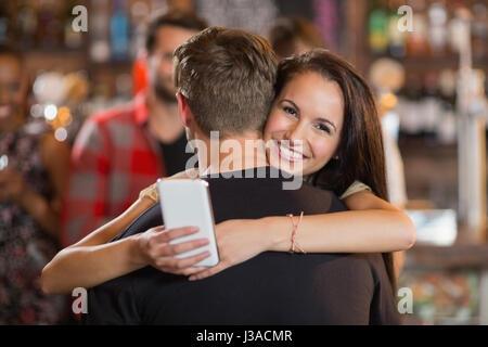 Lächelnde Frau umarmt ihr Freund in der Bar - Stockfoto