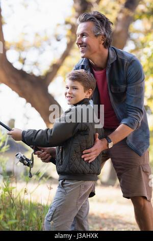 Vater helfen jungen beim Angeln an sonnigen Tag im Wald - Stockfoto