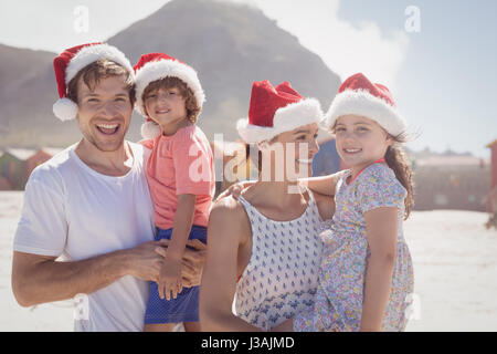 Lächelnd Familie trägt Weihnachtsmütze sonnigen Tag am Strand - Stockfoto