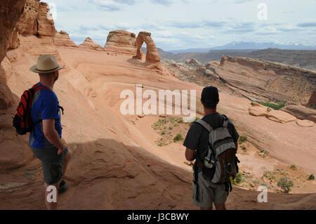 Zwei Wanderer schauen in Richtung der Delicate Arch im Arches-Nationalpark, Moab, Utah. Sie sind die einzigen zwei - Stockfoto