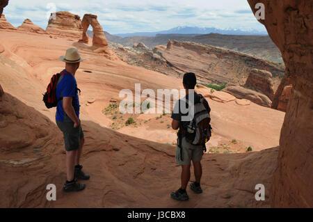 Zwei Wanderer schauen auf den Delicate Arch im Arches-Nationalpark, Moab, Utah aus der Ferne. Sie sind die einzigen - Stockfoto