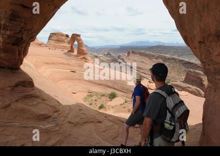 Zwei Wanderer schauen in Richtung der Delicate Arch durch ein anderes Arch im Arches-Nationalpark, Moab, Utah. - Stockfoto