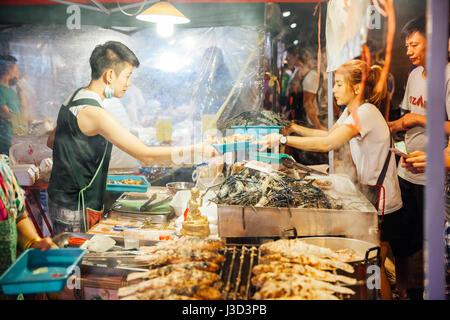 CHIANG MAI, THAILAND - 27 AUGUST: Food Vendor kocht und verkauft Fisch und Meeresfrüchte am Samstag Nachtmarkt (Walking Street) am 27. August 2016 in Chi