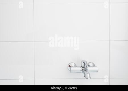 Wasserhahn für die Badewanne auf weißen gefliesten Wand - Stockfoto