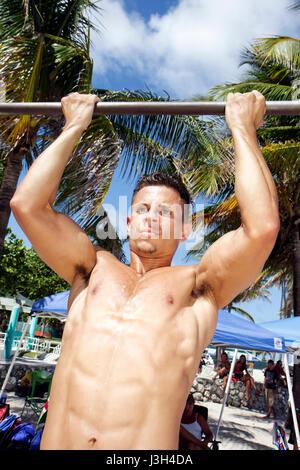 Miami Beach Florida Lummus Park Hispanic Mann Junge Pull-up Fitness fit muskulös Übung Gesundheit Muskeln Tan Sonne - Stockfoto