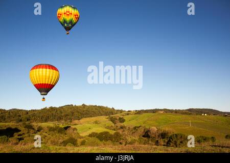 Heißluftballons über Napa Valley Weinberge bei Sonnenaufgang mit blauem Himmel und Kopie. - Stockfoto