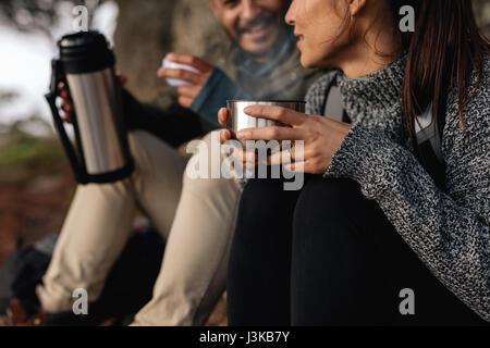 Junge Frau mit ihrem Freund eine Pause auf einer Wanderung. Paar Wandern Rest sprechen und trinken Kaffee. - Stockfoto