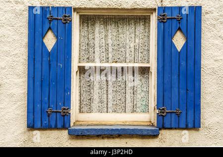 Fenster mit Fensterläden aus Holz, Rautenform geschnitten in Rollläden, Fensterläden lackiert in blau, schön gemusterte - Stockfoto
