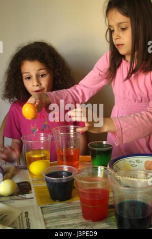Zwei kleine Mädchen, die Spaß sterben Eiern - Stockfoto